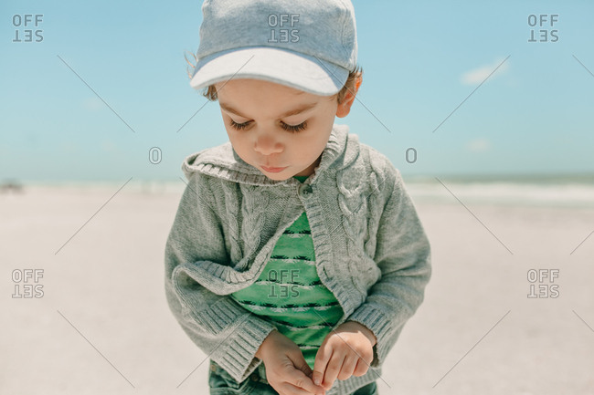 Small toddler boy in hat and sweater looking down at the sand