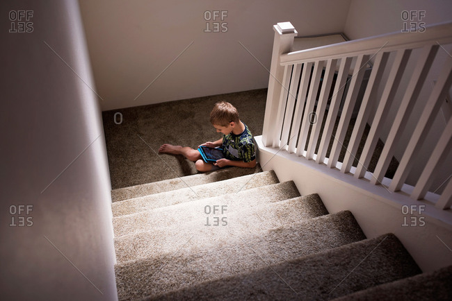 Boy sitting at bottom of stairs playing on tablet