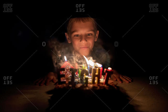 Boy blowing out candles on his eighth birthday