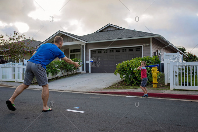 Father pitching baseball to son in street