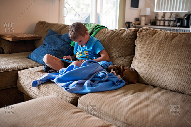 Boy playing tablet and cuddling with boxer puppy on couch