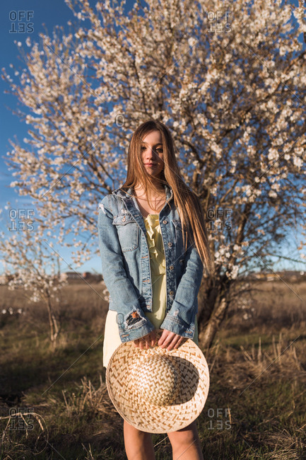 Pretty young woman with hat standing at blooming tree in nature