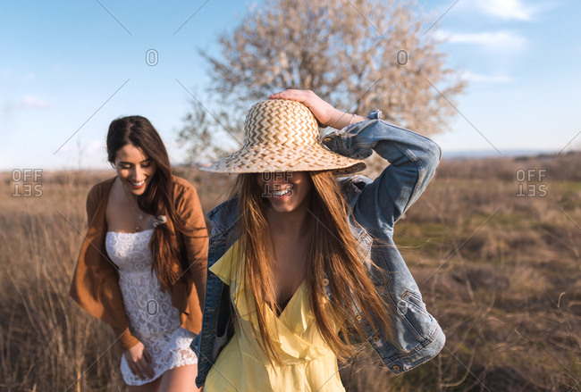 Cheerful young pretty women holding hands and walking on field in sunny day