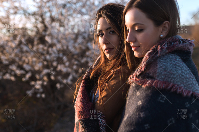 Pretty young women wrapped in plaid standing at blooming tree in nature
