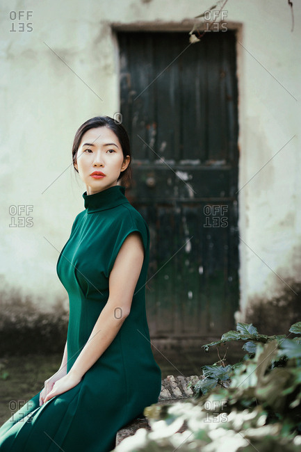 Attractive Asian woman in green dress sitting at grungy house and looking away