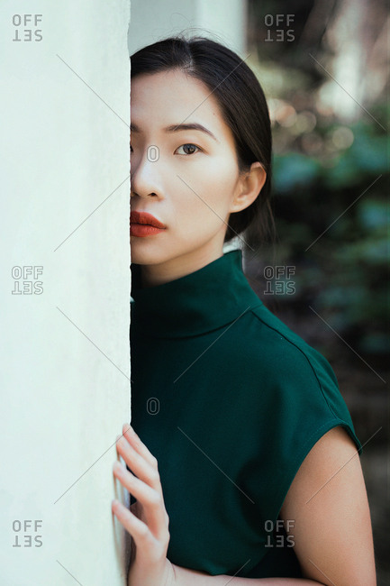 Young Asian woman in green dress looking at camera and leaning on white wall