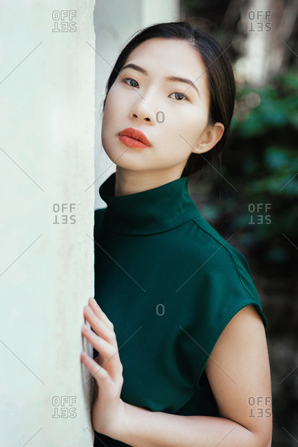 Asian woman leaning on wall