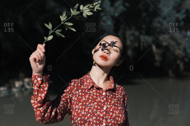 Young Asian woman in red dress holding branch with shadow on fence at pond in nature