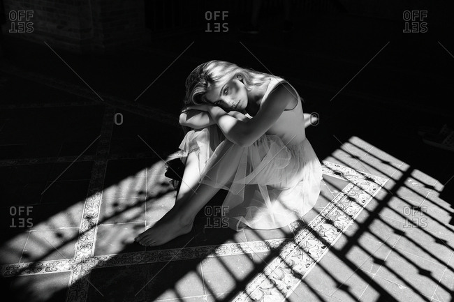 Black and white shot of woman in light white dress sitting on tiled floor in shadow of blinds looking at camera