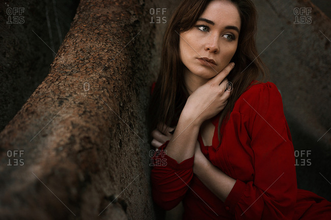 Sensual brunette wearing red dress and sitting under huge tree in roots looking away dreamily