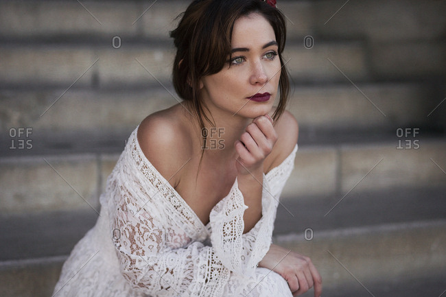 Young sensual brunette in white lace dress sitting on steps looking away