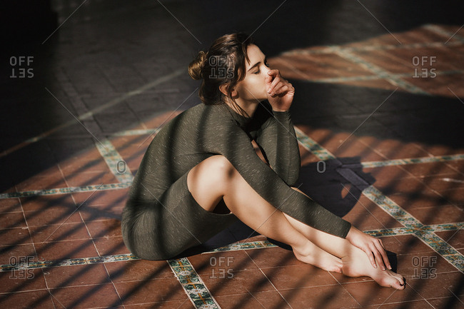Sensual girl sitting on floor in sun rays