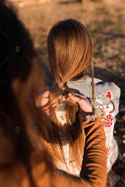 Crop woman braiding hair of girlfriend in sunny nature