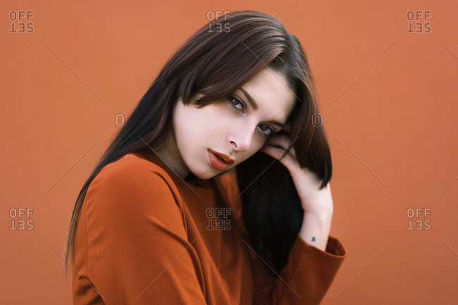 Side view of emotionless model in brown outfit and hairstyle touching face and looking at camera