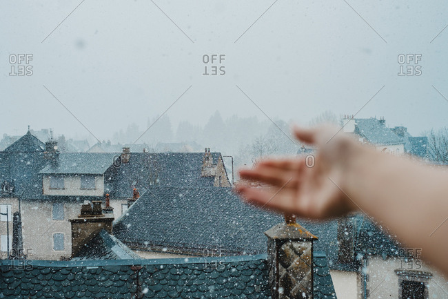 Hand of unrecognizable person pulling hand to falling snowflakes on background of town roofs
