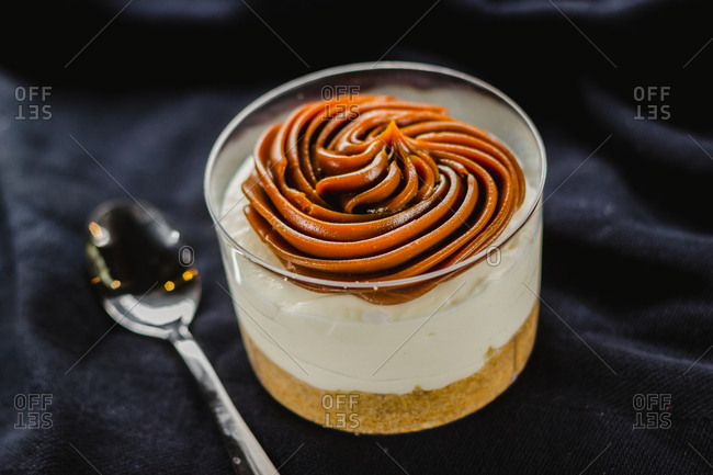 Close-up of creamy dessert composed in cup and topped with delicious cream served on black with spoon
