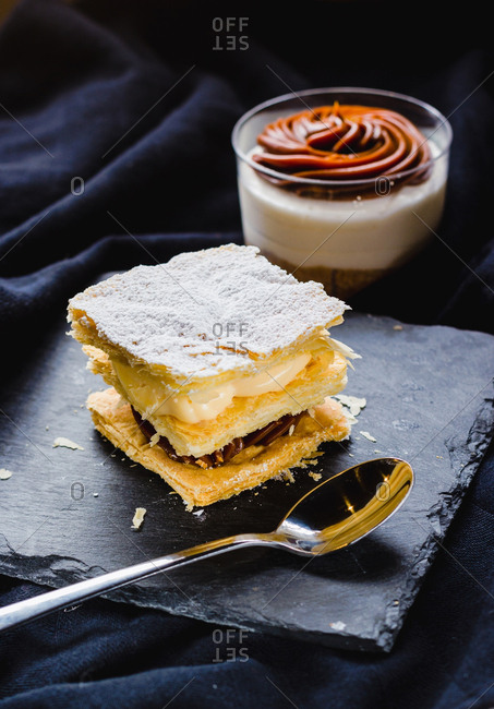 Close-up of puff pastry dessert with creams on plate and dessert in cup composed on soft textile