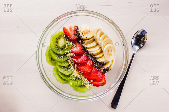 Flat lay of bowl filled with sliced kiwi and strawberry and banana topped with seeds and nuts