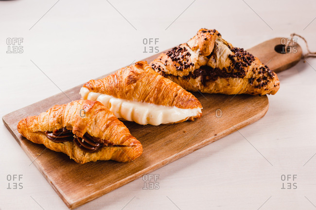 Wooden board with three croissants stuffed with various and delicious creams on white surface