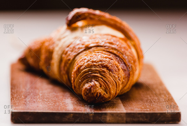 Close-up of delicious freshly baked golden croissant with golden crust on wooden board