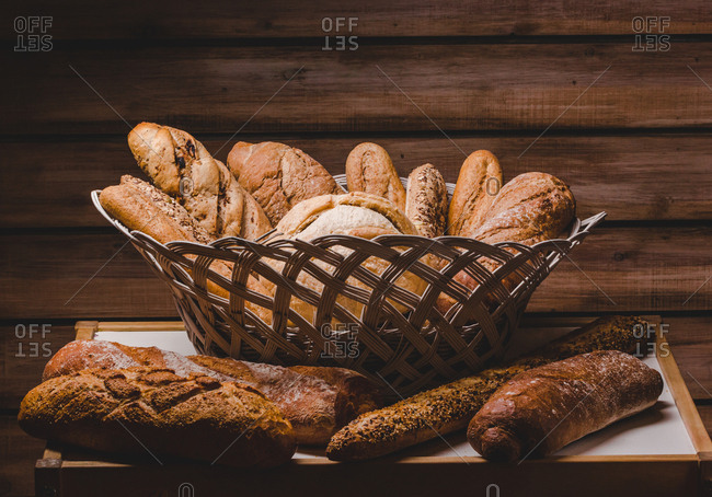 Beautiful rustic arrangement of basket with bread loaves and buns and baguettes on wooden background