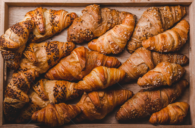 From above of assorted golden baked croissants with different toppings on wooden board