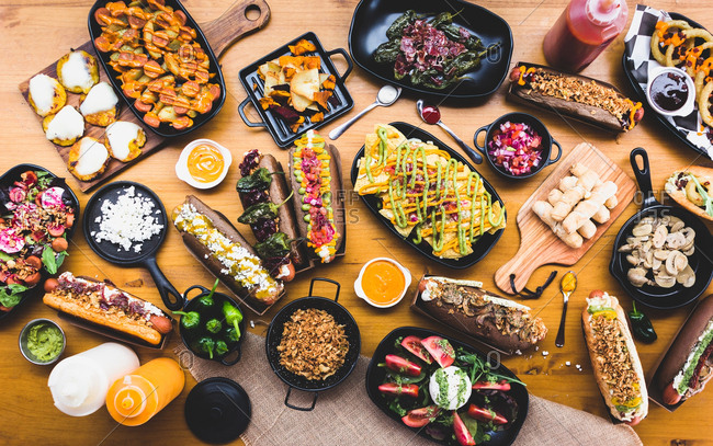 Flat lay of table served with great amount of various snacks and hot dogs with sauces and spices,