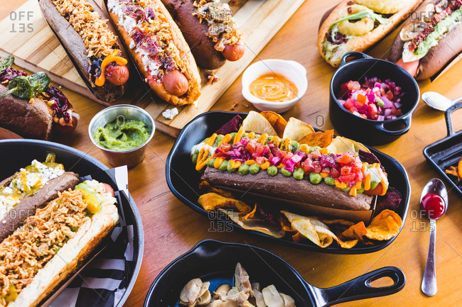 Flat lay of great amount of delicious food of hot dogs and snacks served on wooden table