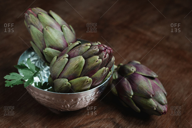 three artichoke in a bowl over a wooden table