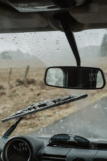 Interior of a car driving on asphalt road in cloudy snowy day