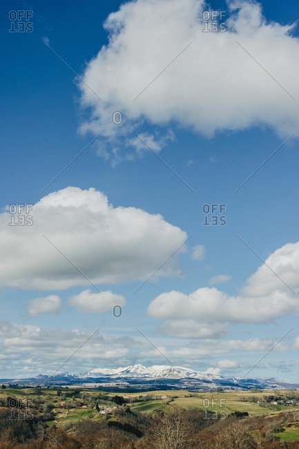 Picturesque view to green field and snowy hills under clouds in blue sky
