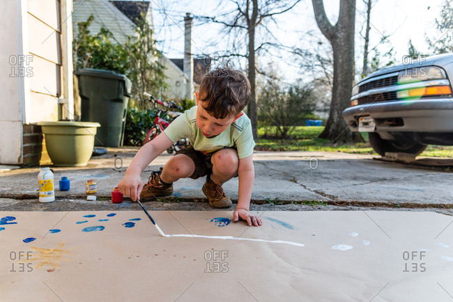 Little boy painting in driveway