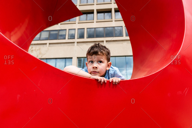 Young boy sitting in large red structure