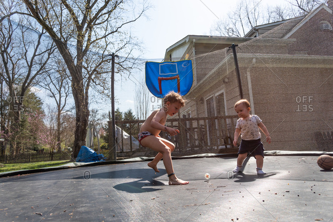 Two little boys jumping on a trampoline