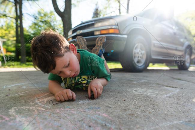 Little boy touching a slug in a driveway