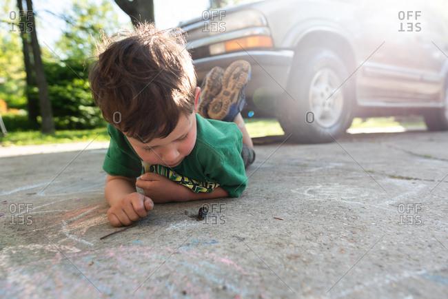 Little boy looking at slug in a driveway