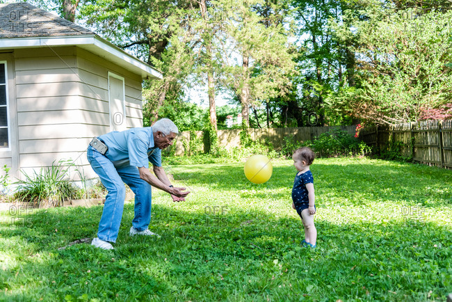 Toddler and grandfather tossing a ball in the backyard