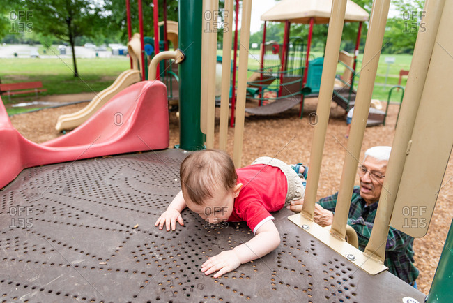 Grandfather helping toddler climb up to a slide at a playground