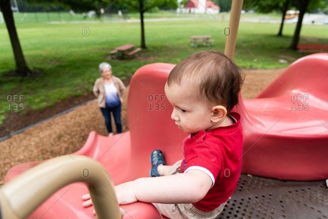 Grandmother watching toddler slide down a slide
