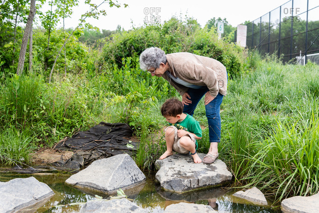 Grandmother and grandson looking into creek