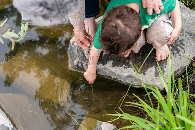Boy and his grandmother looking into creek