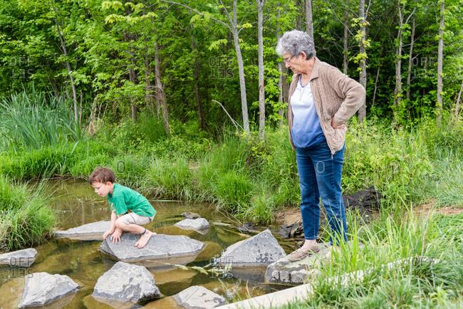 Grandmother and grandson exploring a creek