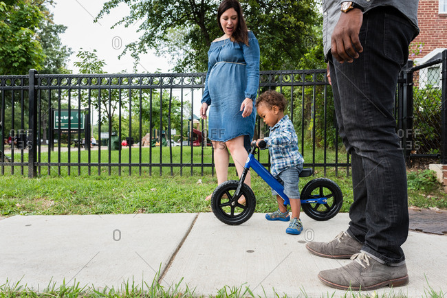 Multiracial toddler riding bike beside mom and dad