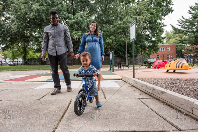 Multiracial toddler riding bike by mom and dad at a park
