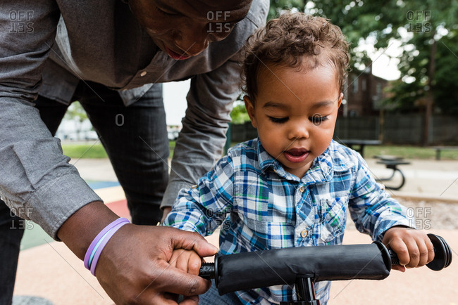 Father helping toddler son ride a bike