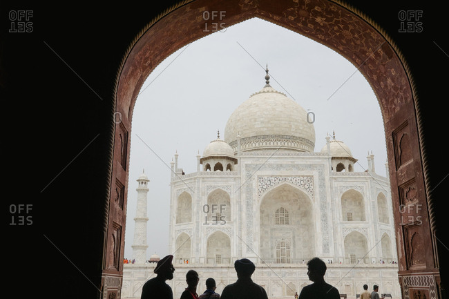 Agra, India - August 4, 2017: Silhouette of tourists observing the Taj Mahal