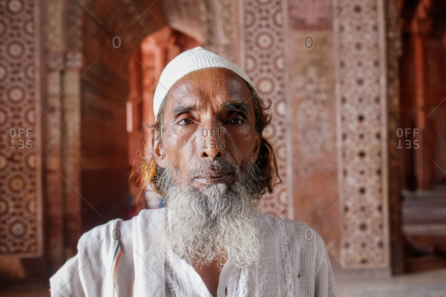 Fatehpur Sikri, India - August 5, 2017: Old Indian man at a tomb in Fatehpur Sikri, India
