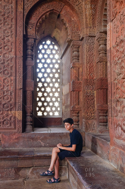Teen boy sitting inside the Qutb Minar in New Delhi, India
