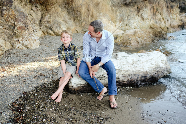 Father and son sitting on oceanside log together