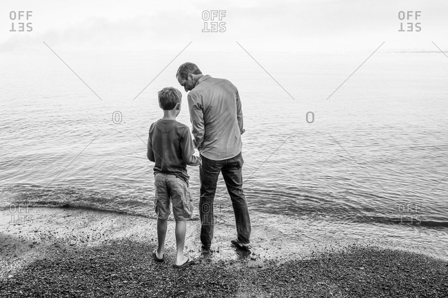 Father and son standing on beach looking out at water